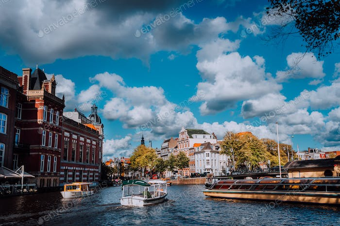 Bright blue sky and fluffy clouds over Amstel in Amsterdam Netherlands, landmark old european city