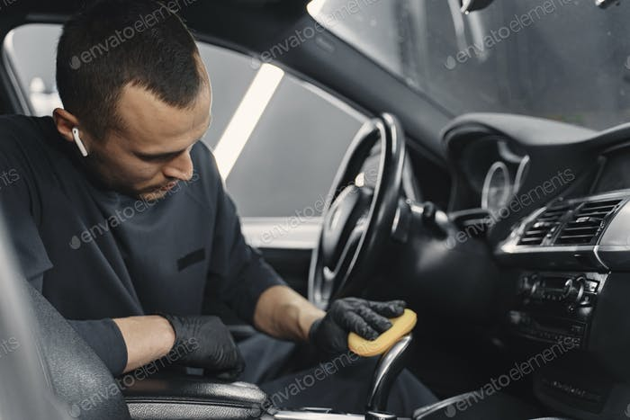 Mann polnischen Salon des Autos in einer Garage