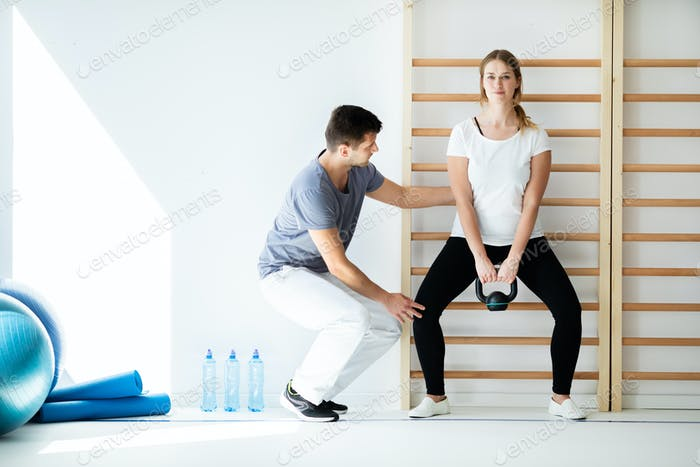 Professional physician helping his patient exercise with weights