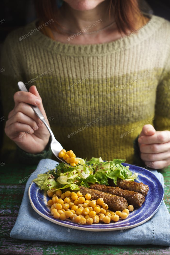 Woman eat cevapcici on the wooden table vertical