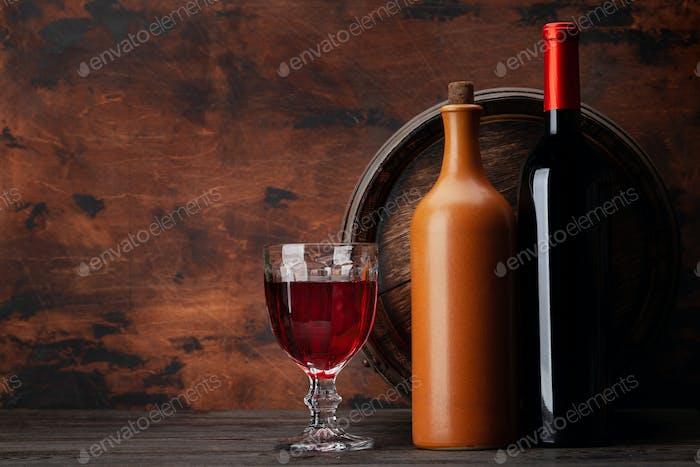 Weinflaschen und altes Holzfass