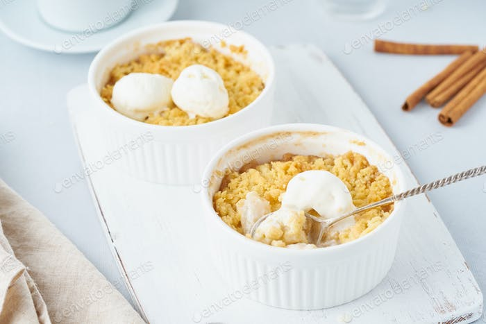 Apple crumble with ice cream, spoon with streusel. Morning breakfast on a light gray table