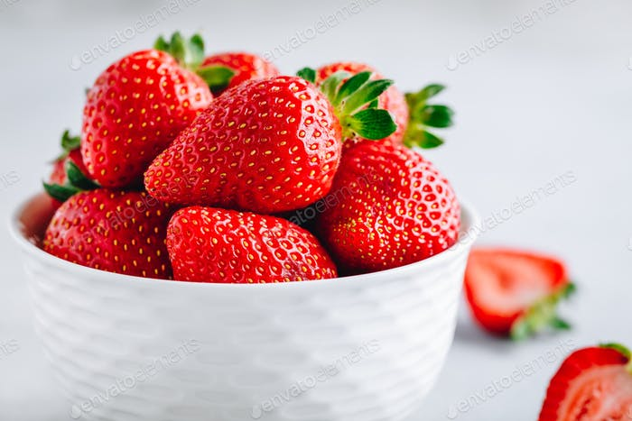 Fresh ripe delicious strawberry in a white bowl on a grey stone background
