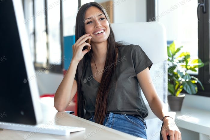 Smiling young business woman talking on mobile phone while sitting in the office.