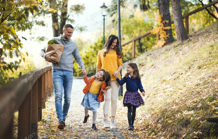 A young family with children walking in park in autumn.