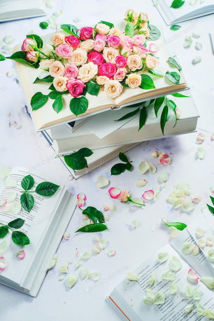 Spring reading concept. Stack of white books with flowers and petals. Feminine still life in high
