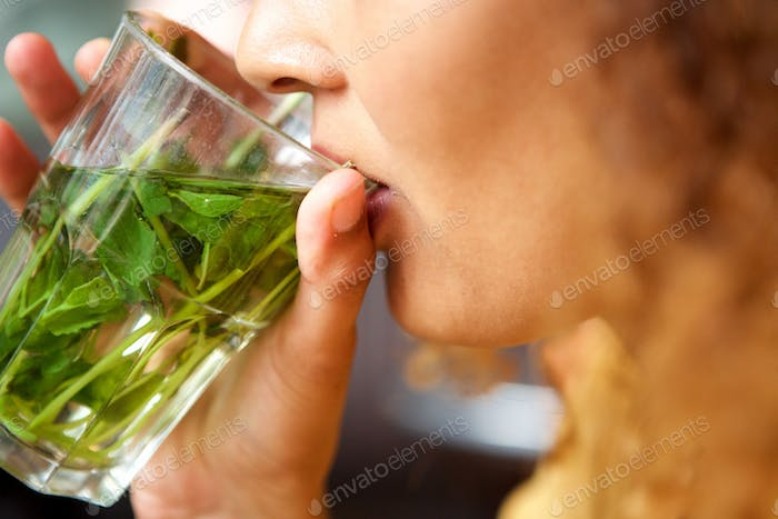 female hands holding glass of mint tea to mouth