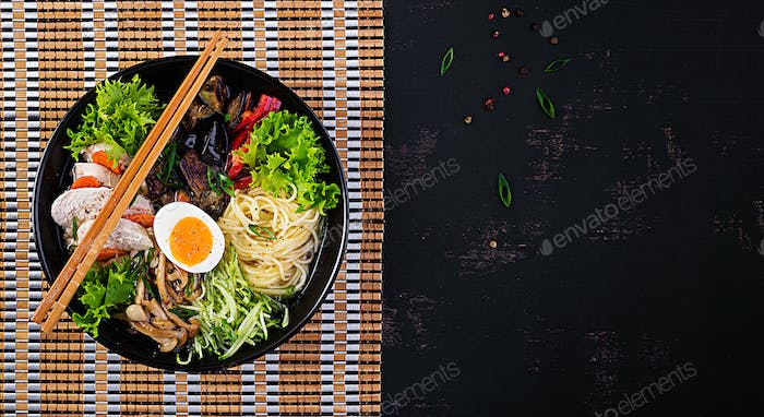 Japanese ramen soup with chicken, egg, shimeji mushrooms and eggplants on dark wooden background.