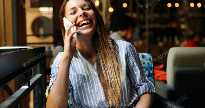 Beautiful woman talking on phone in restaurant