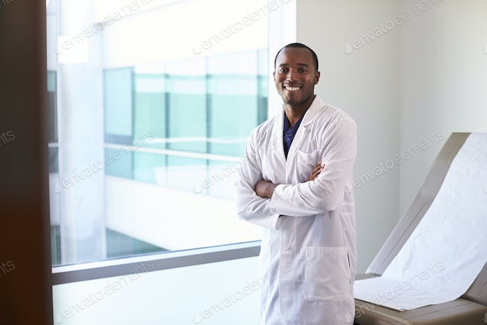 Portrait Of Male Doctor Wearing White Coat In Exam Room