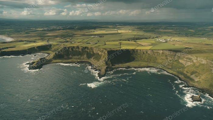 Cliff ocean Ireland shore aerial view: green grassy valley with little farms in Irish countryside