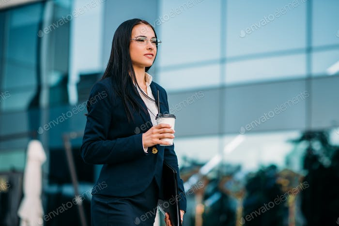 Business woman in glasses with coffee in hands