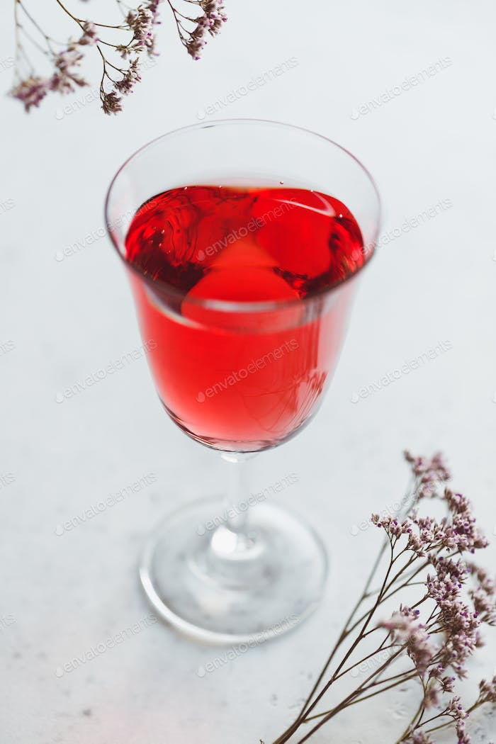 Glass of pink wine on a white table with flowers.