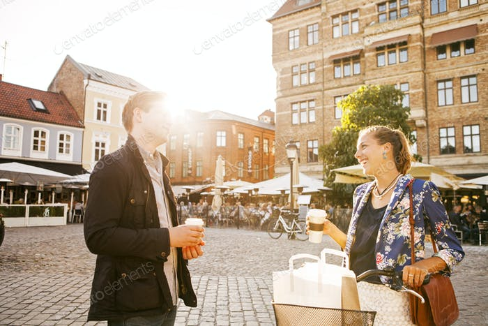 Cheerful couple looking at each other while holding disposable cups in city