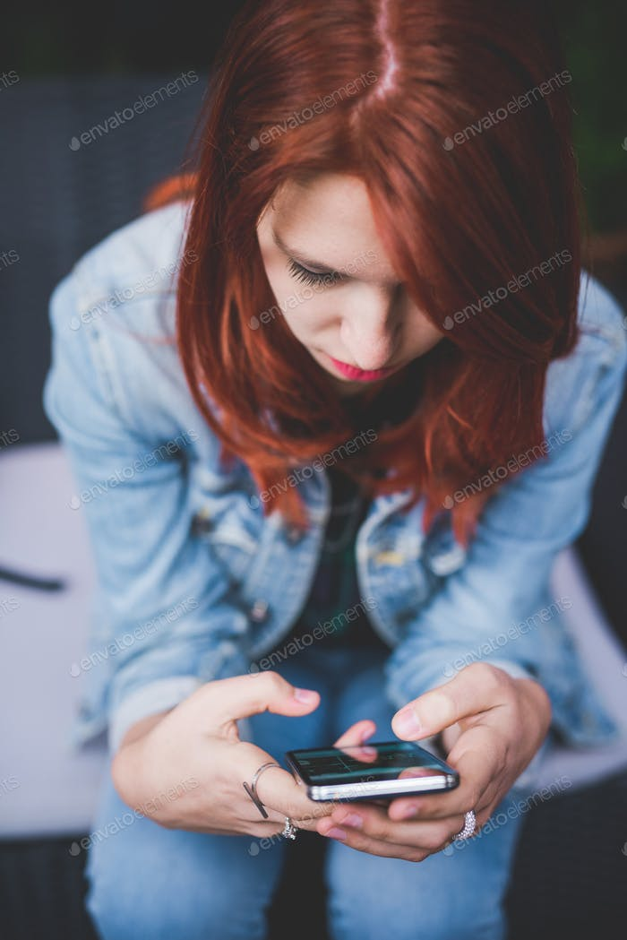 Young handsome caucasian redhead woman holding a smartphone look