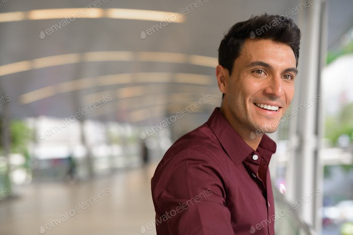 Young happy Hispanic businessman thinking on the footbridge