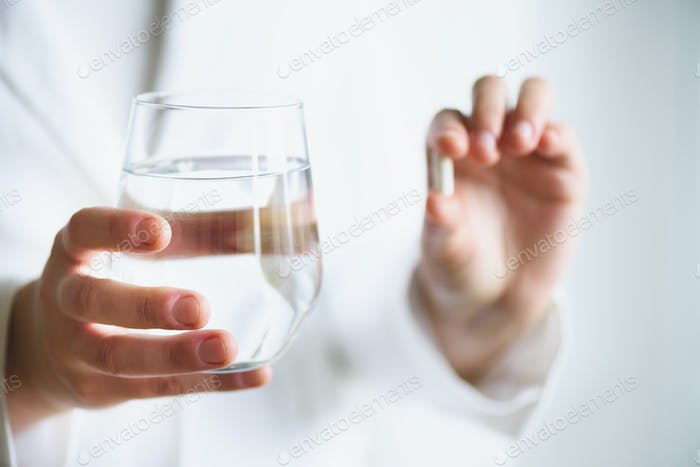 Doctor holding a glass of water with drug, pills, white background. Copy space. Medicine concept