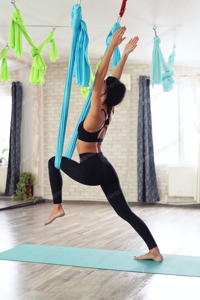 Взрослый женщина практикует анти-гравитация йога позиции в студия