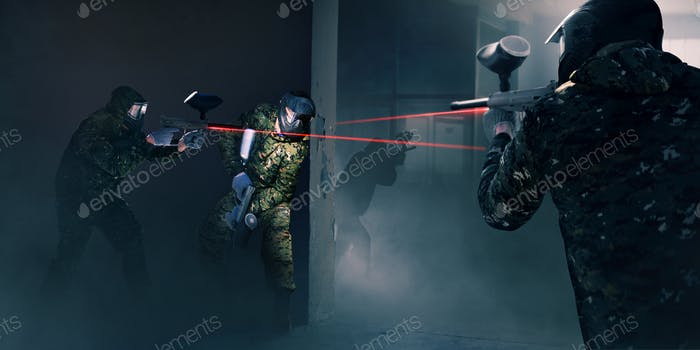Paintball team in battle, guns with a laser sight
