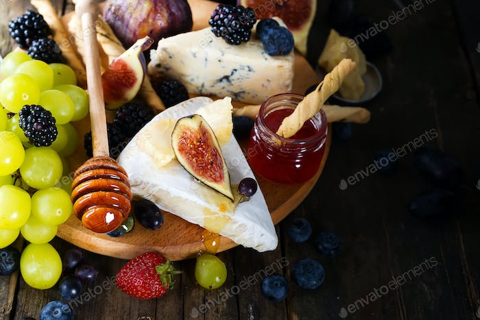 Cheese plate served with wine, jam and stick with honey