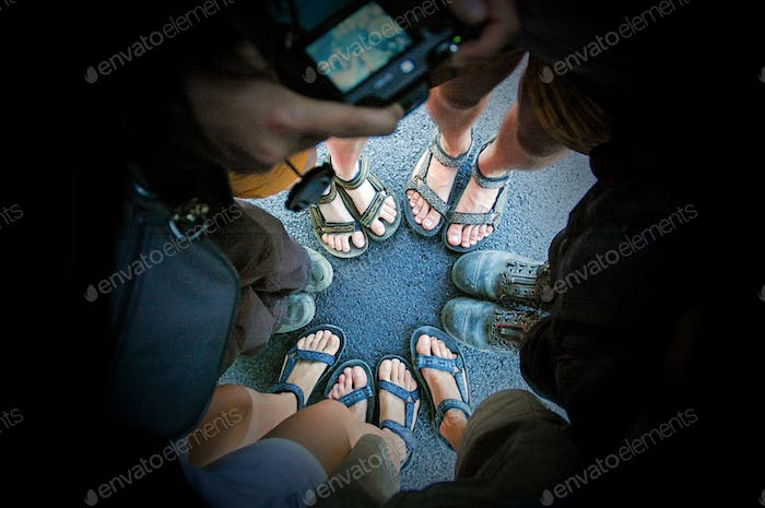 Top view of friends legs and feet in sandals and boots standing in circle on asphalt road