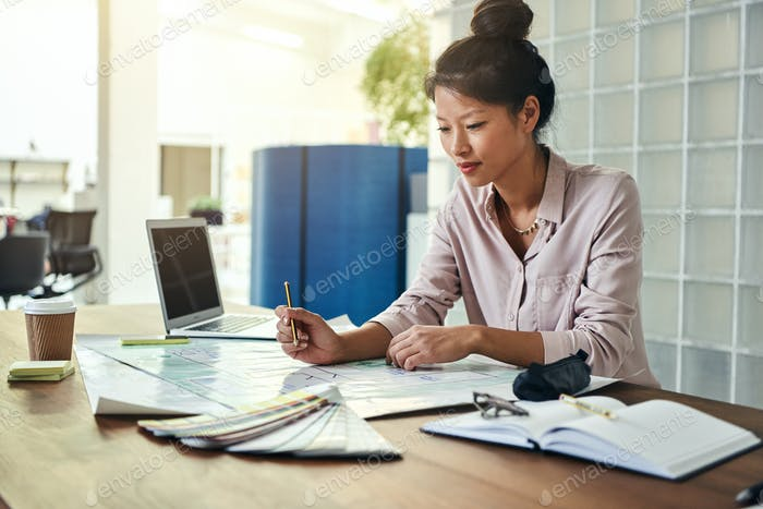 Young Asian designer sitting at her desk looking over blueprints