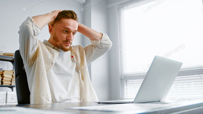 Depressed guy in yellow shirt looks at laptop with lost internet connection holding hands on head