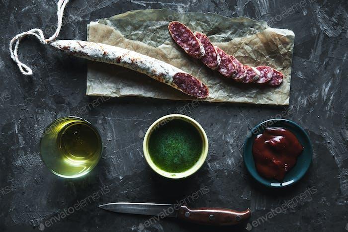 Wurst auf einem dunklen Hintergrund mit Elementen des Kochens. Gurke, Zwiebel, Ketchup