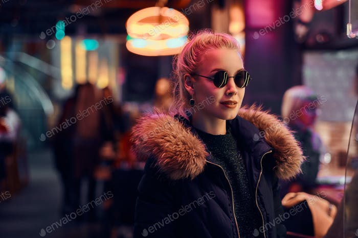 A sensual girl standing in the night on the street. Illuminated signboards, neon, lights.