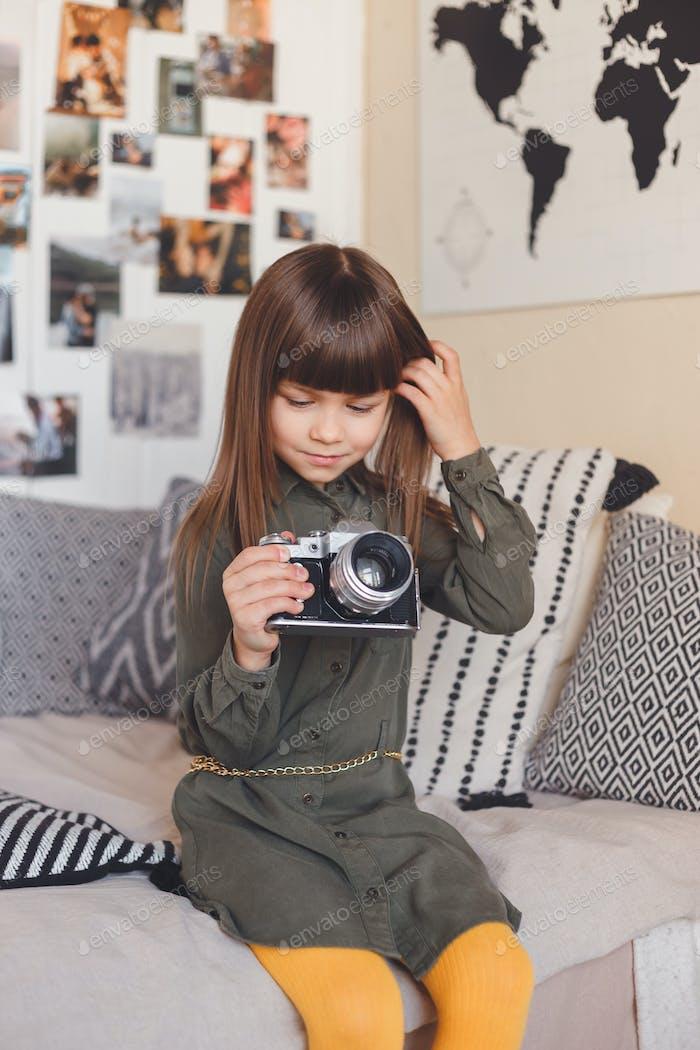 Kleines Mädchen mit einer alten Kamera. Möchte Fotograf werden