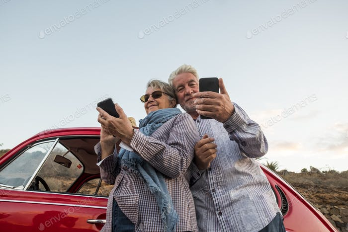 Happy elderly senior couple use mobile phones outdoor near a red car