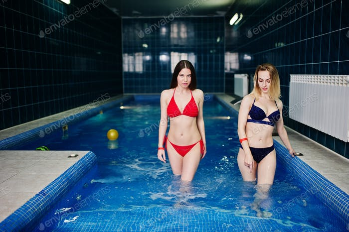 Two sexy girls in swimsuit having rest in sauna swimming pool.