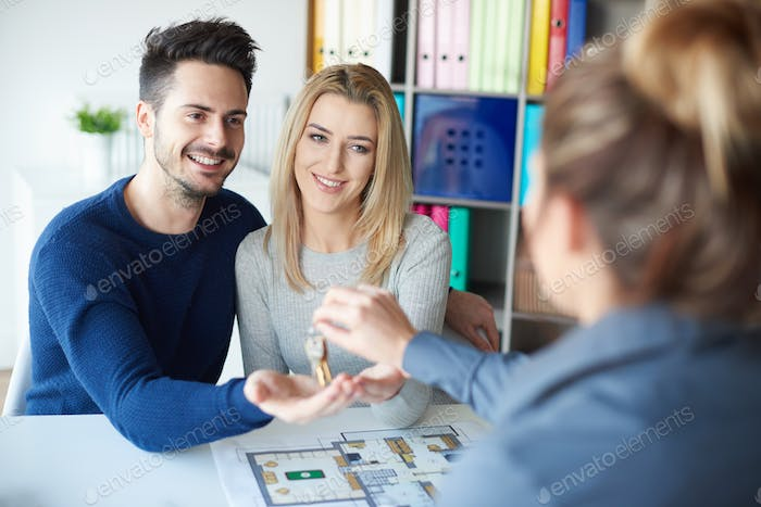Estate agent giving keys to couple