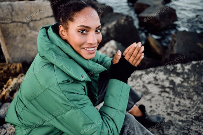 Pretty stylish African American girl in down jacket warming hands happily on rocks by the sea