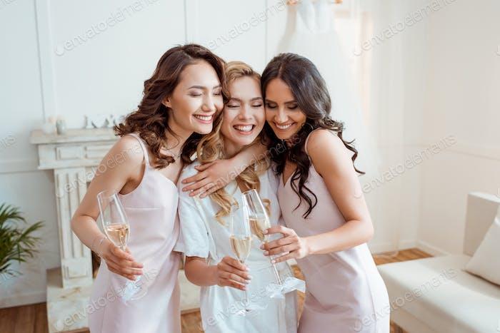 Braut mit Brautjungfern umarmen und Toasten mit Champagner