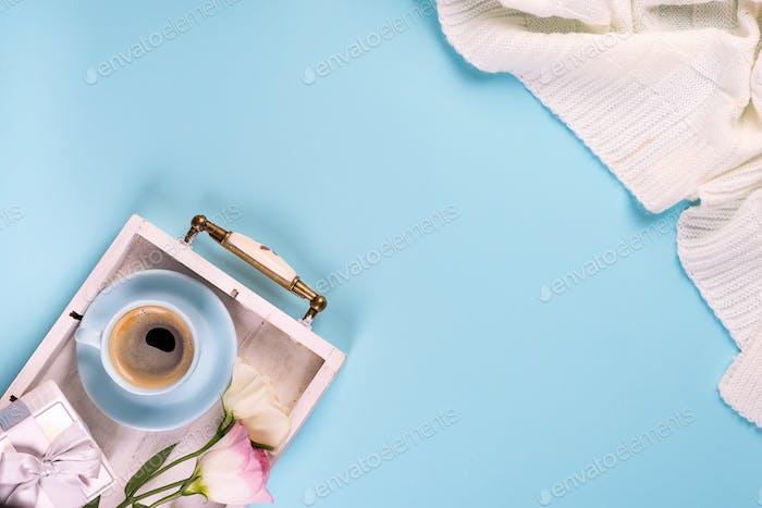 Mit einer Tasse Kaffee, Blumen Eustoma und Geschenk-Box auf der Decke auf einem blauen Hintergrund, flach lag Kopie