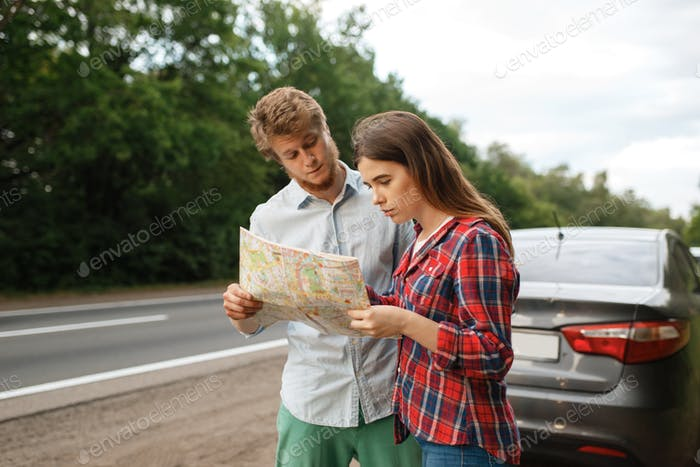 Car tourists looking on map, road travel