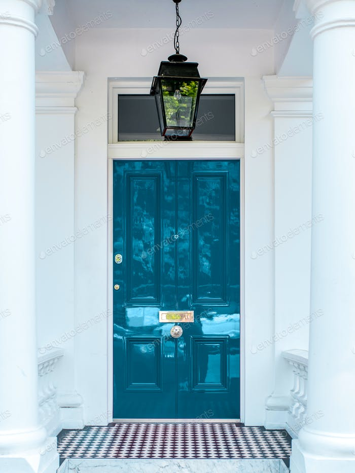 Beautiful blue door in a white house facade in Notting Hill