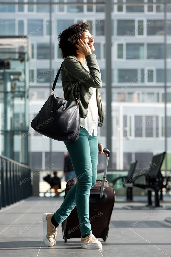Happy travel woman walking at station with suitcase and talking on cellphone