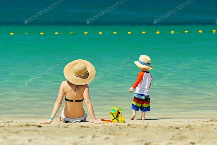 Dos Año de edad niño jugando con madre en Playa