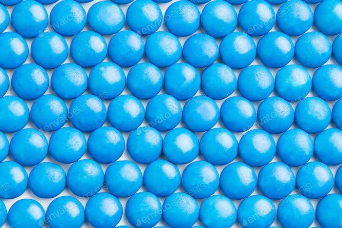 Close up neatly arranged blue milk chocolate candies crisp shell