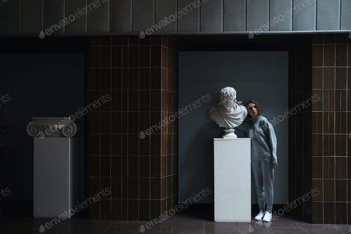 Full-length shot of woman standing near bust