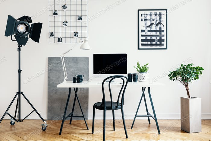 Real photo of a home office interior with a professional lamp, d