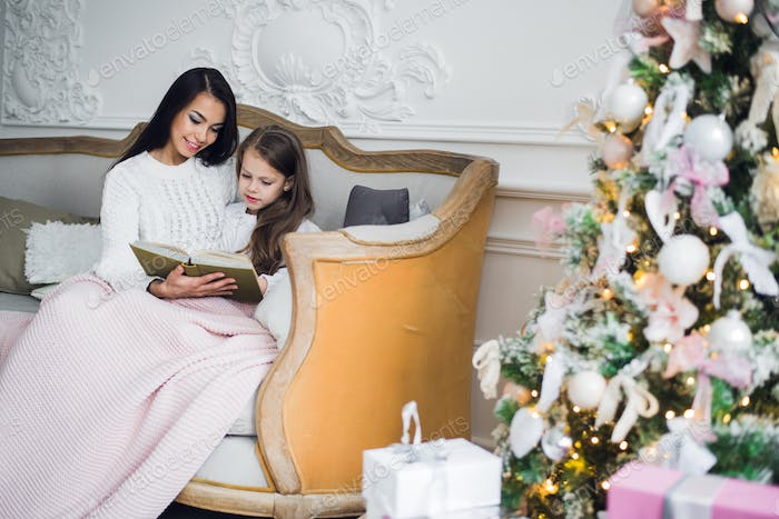 Two happy girls, mother and daughter siting on a sofa in Christmas decorated room.