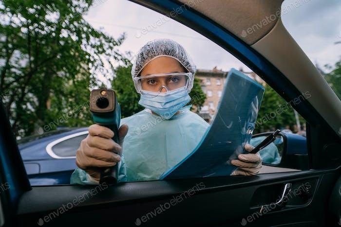 Arzt Frau verwenden Infrarot-Thermometerpistole, um die Körpertemperatur zu überprüfen