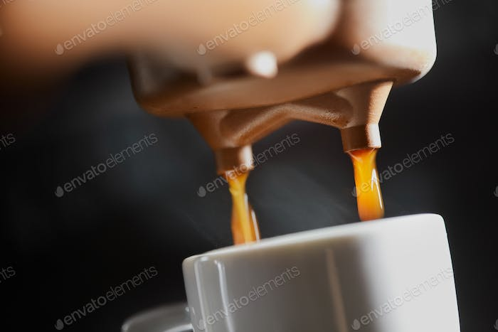 Macro photo of making fresh espresso coffee in a coffee machine. Breakfast