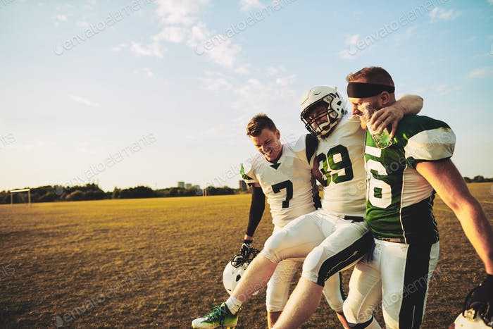 American football players carrying an injured teammate off the field