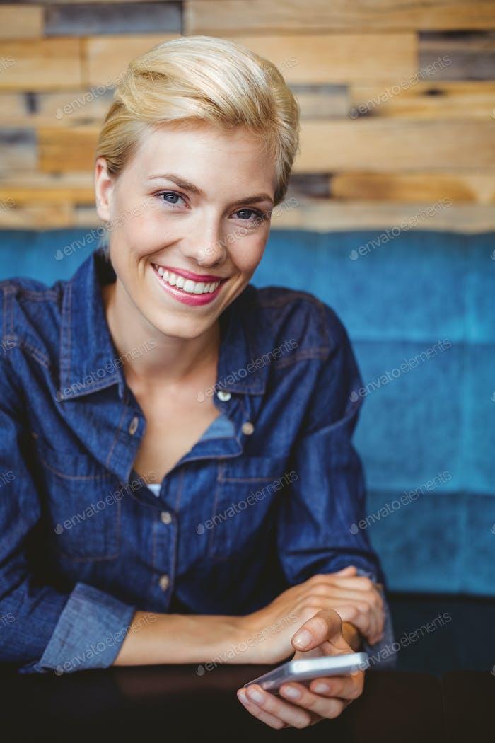 Portrait of a smiling pretty blonde sending a text message