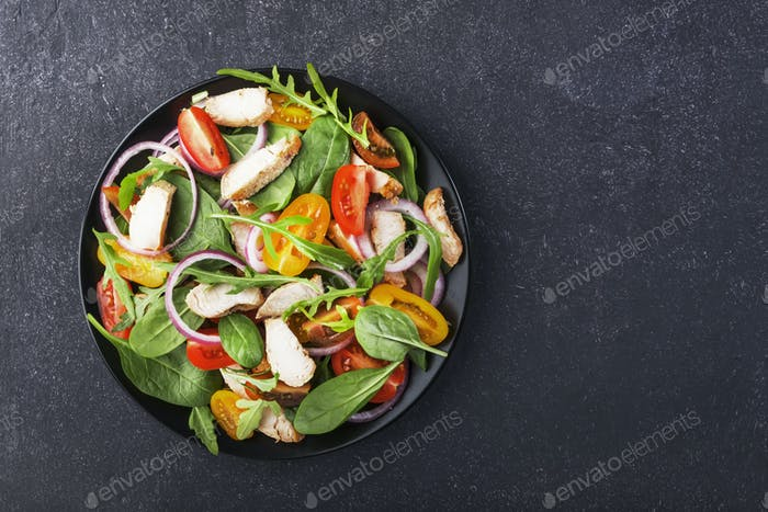 Spring salad with spinach, grilled chicken, cherry tomatoes, arugula