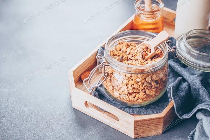 Zutaten für gesundes Frühstück - Müsli, Milch oder Joghurt und Honig. Granola im Glasgefäß auf Tablett